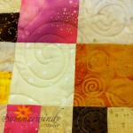 Swirls: Semi-custom quilting on colorful patchwork pieced by Harriet R.