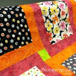 Swirls and leaves: Custom quilting on colorful flower quilt pieced by Kathy H.